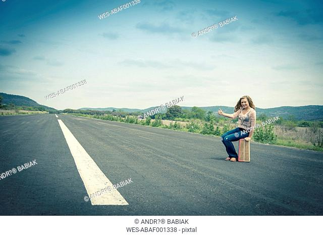 Young woman hitchhiking at empty street