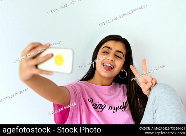 Teenage girl using smartphone on bed and taking photos