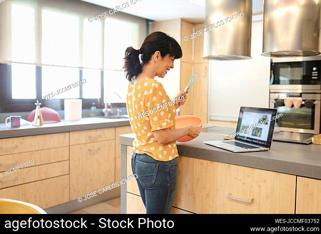 Happy woman preparing food wile learning through laptop in kitchen at home
