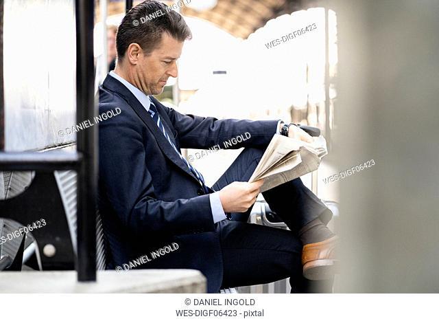 Businessman reading newspaper on station platform