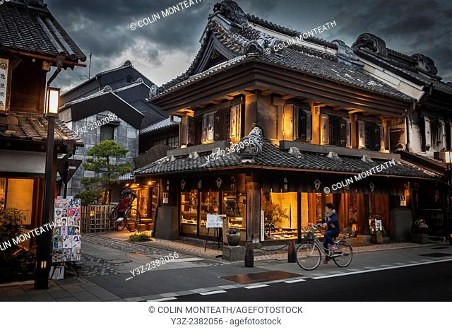 Cyclist rides past craft shop at dusk, rain storm approaches, Magome, near Tokyo, Japan