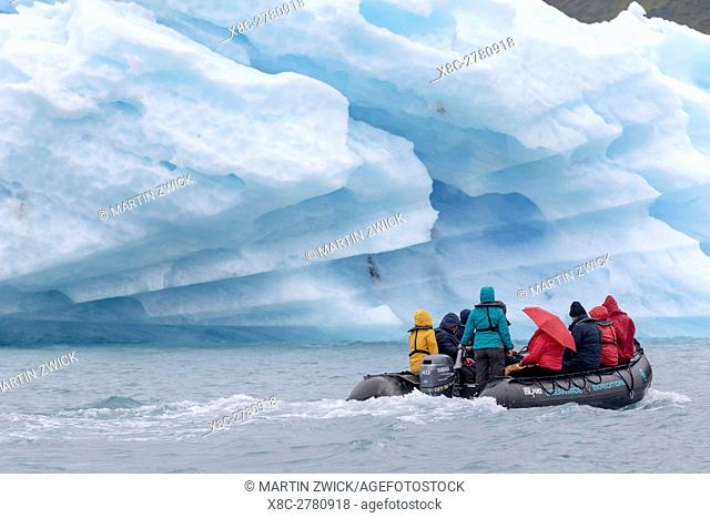 Tourists in Zodiac with icebergs drifting in the fjords of southern greenland. America, North America, Greenland, Denmark