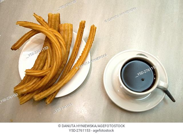 hot chocolate dipping sauce served in a cup and plate of churros, San Gines chocolateria in Madrid, Spain, Europe