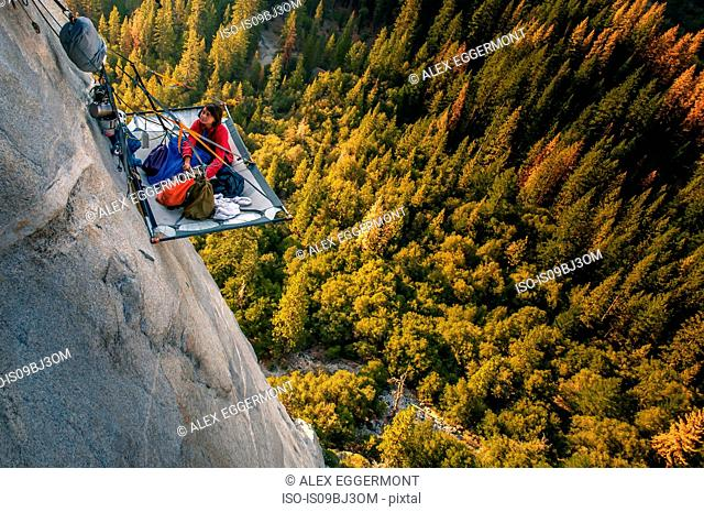 Woman looking up from portaledge on triple direct, El Capitan, high angle view, Yosemite Valley, California, USA