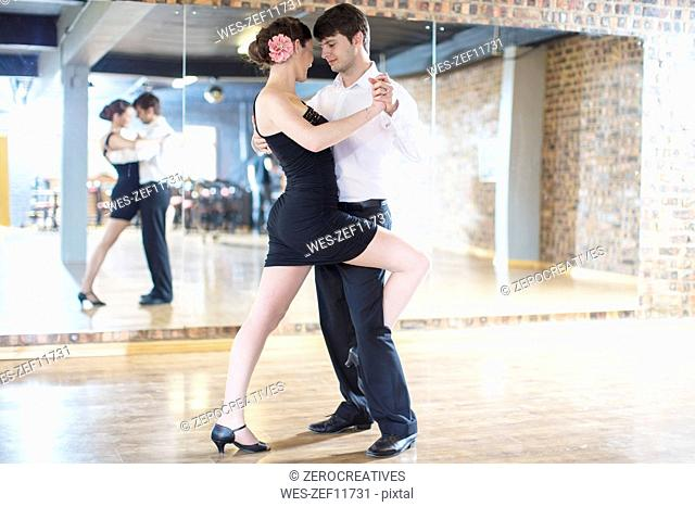 Couple dancing salsa in studio