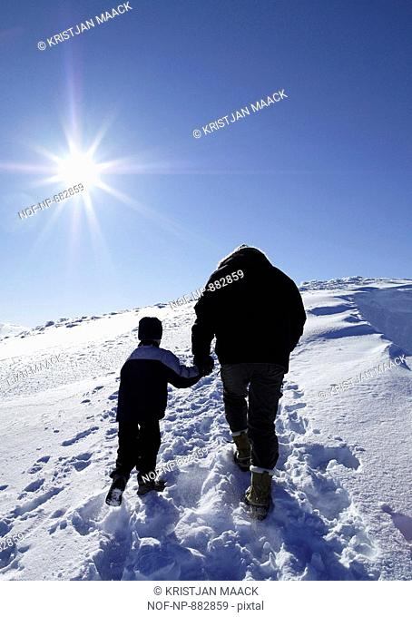 Low angle view of a boy holding hand of his father and walking on a snow covered landscape