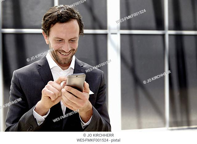 Businessman using smartphone in a modern building