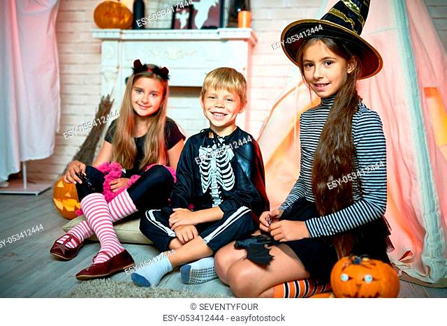 Portrait of three children wearing Halloween costumes posing looking at camera sitting on floor in decorated studio