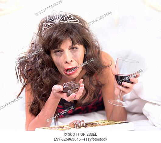 Sobbing mature woman wearing a tiara crying and cramming chocolates in her bedroom