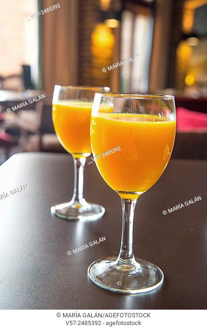 Two glasses of orange juice in a cafeteria