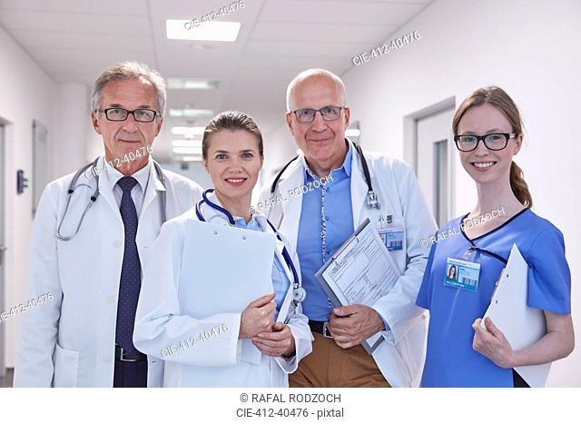 Portrait confident doctors and nurse in hospital corridor