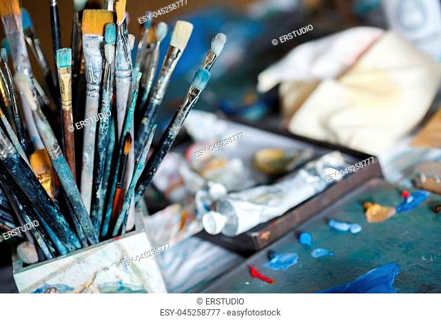 many different painting brushes in the artist's workspace