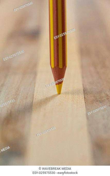 Yellow colored pencil on wooden background