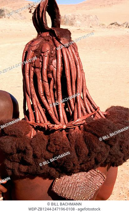 Namibia Africa remote nomadic Himba tribe young woman with braids and traditional dress close up of hair in desert of Hartmann Berge in Namib Desert