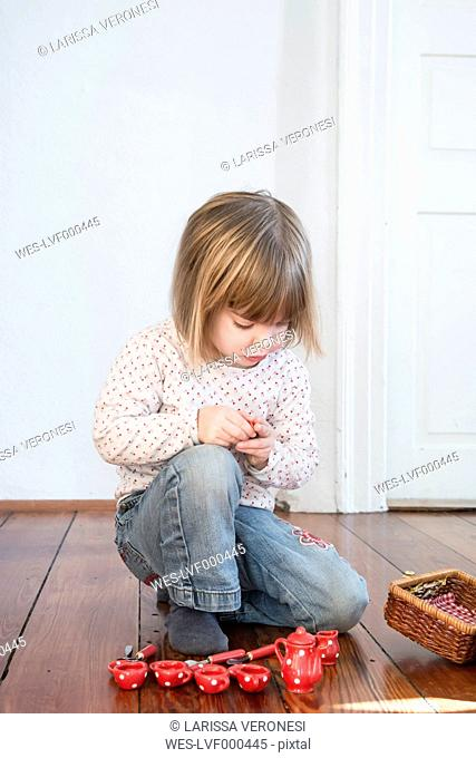 Little girl playing with dolls china set