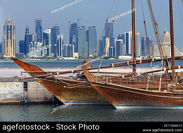 Dhow traditional sailing in Corniche promenade. Behind the skyscrapers of the skyline of the financial area of Doha, the capital of Qatar in the Arabian Gulf...