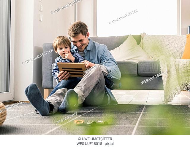 Father and son sitting on floor, using digital tablet