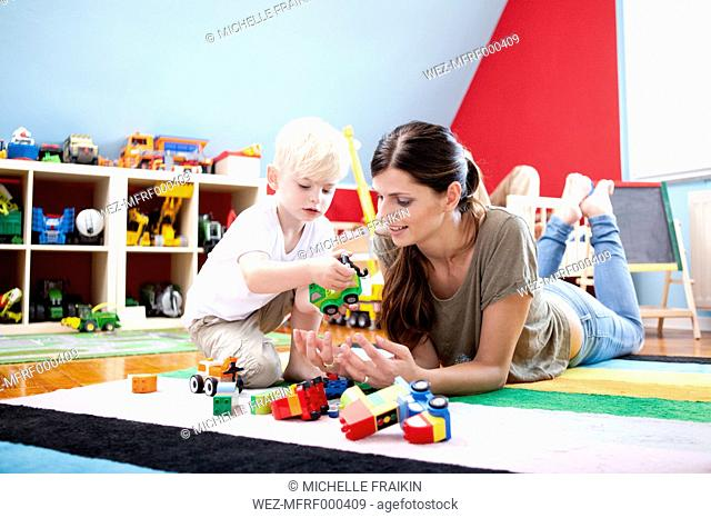 Mother playing with her little son on the carpet of children's room