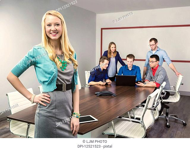 A beautiful young millennial business woman working on her tablet in a conference room with her co-workers; Sherwood Park, Alberta, Canada