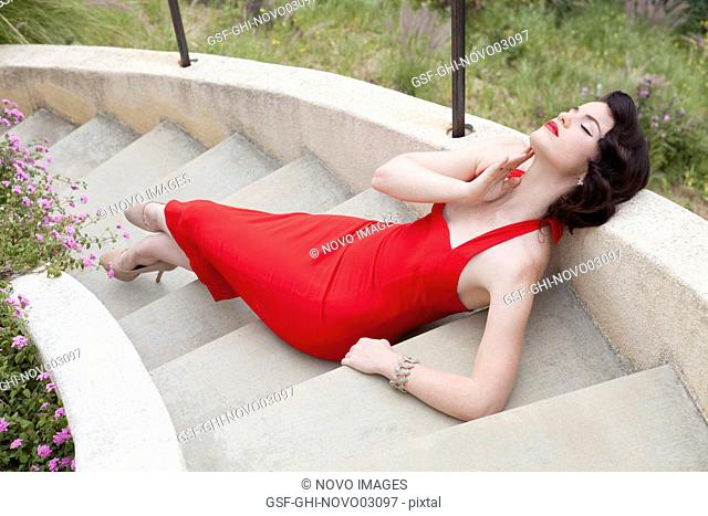Fashionable Young Adult Woman in Vintage Red Dress Lounging on Outdoor Steps