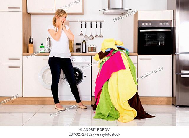 Exhausted Young Woman Standing Near Pile Of Untidy Clothes In Kitchen