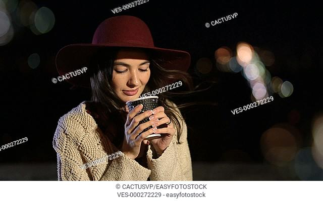 Attractive girl enjoying cup of coffee at night