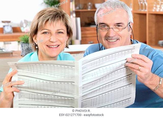 Mature couple reading a newspaper together