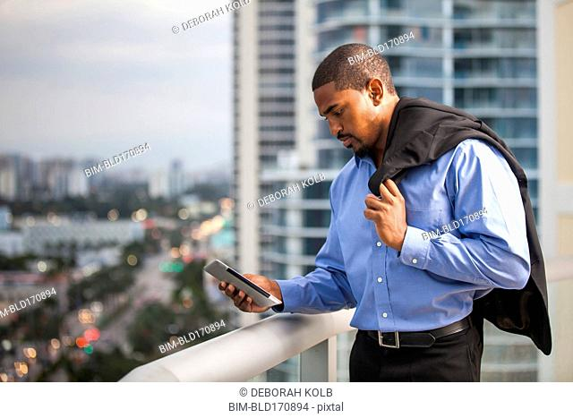 African American businessman using cell phone on urban balcony