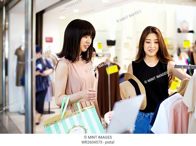 Two young women with long brown hair in a shopping centre