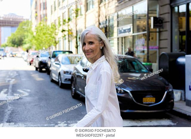 USA, Brooklyn, portrait of smiling mature woman crossing the street