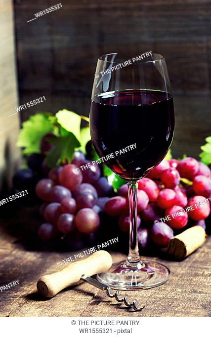 Red wine and red grapes on wooden background