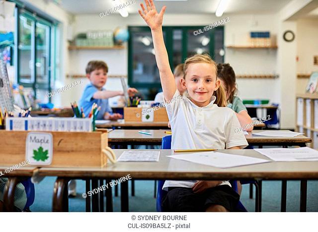 Schoolgirl with hand raised in classroom at primary school
