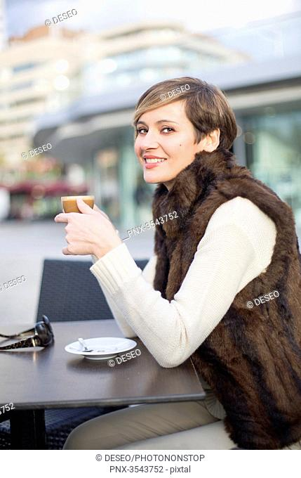 Pretty woman enjoying a coffee outdoor smiling at camera