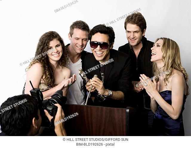 People congratulating celebrity on award