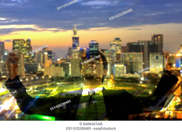 double exposure business man so glad as if he has got to success something and blurry night cityscape with sunset sky background , soft focus