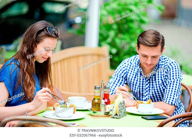 Happy couple enjoying sitting in outdoor cafe