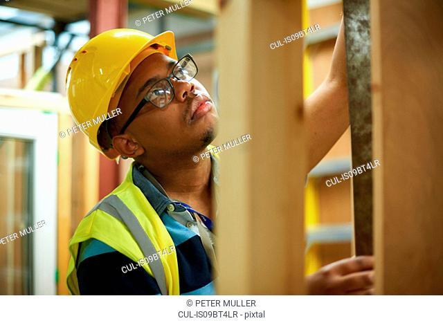 Male higher education student building wooden framework in college workshop