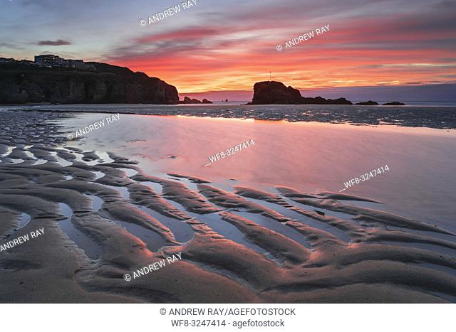 Sand ripples captured at sunrise on the beach at Perranporth on the north coast of Cornwall, with Chapel Rock in the distance