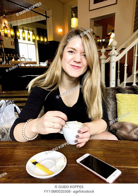 Tilburg, Netherlands. Young adult, caucasian woman playing with her smartphone while visiting a cafe and restaurant for a cappuchino