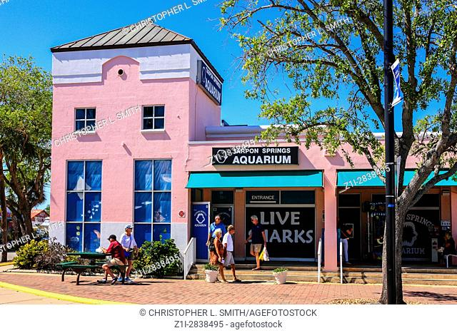 People outside the Pink colored Tarpon Springs Aquarium building in Florida