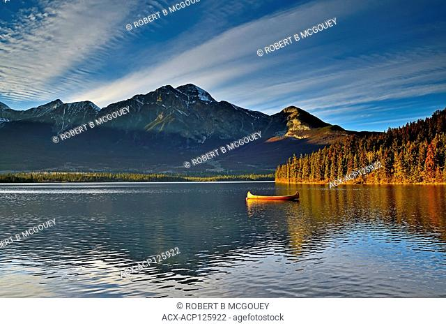 A landscape image of a cedar strip canoe moored on Pyramid Lake in Jasper National Park Alberta Canada