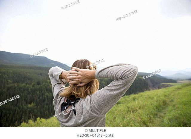 Woman with hands behind head looking at remote rural field view