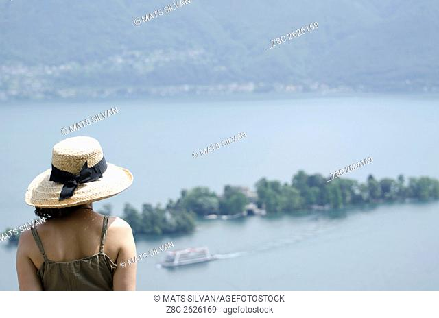 Woman with a straw hat watching Brissago islands and passenger ship on alpine lake Maggiore in Ticino, Switzerland