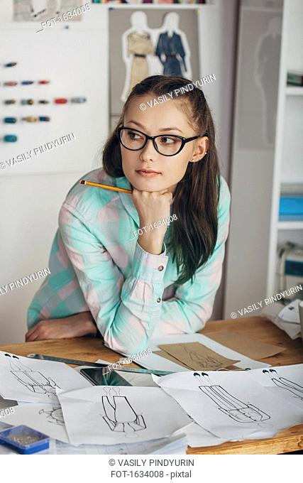 Thoughtful beautiful fashion designer looking away at workbench in studio