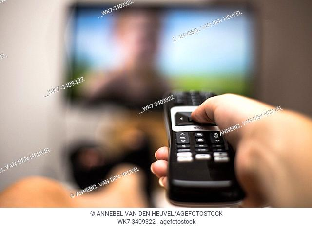 Hand Holding Use Remote Control and Watching TV in House on a colorful flatscreen modern design
