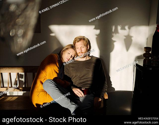 Relaxed couple sitting on bench in sunlight at home