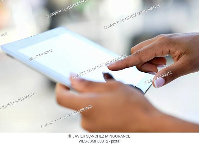 Close-up of woman's hands using tablet outdoors