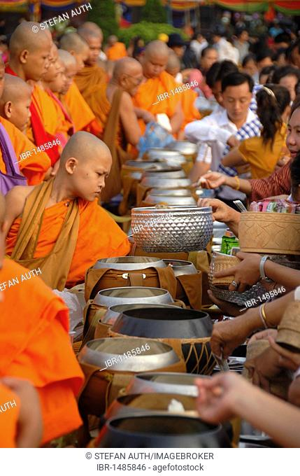 Theravada Buddhism, That Luang Festival, Tak Bat, monks standing behind alms bowls, hands, believers, pilgrims giving alms, orange robes, Vientiane, Laos
