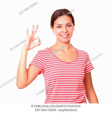 Portrait of young girl on red t-shirt with great job gesture smiling at you on isolated white background