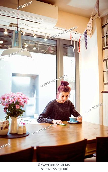 Hipster drinking a cup of coffee while using a smartphone